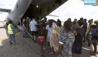 In this image made from video taken on March 21, 2019, storm evacuees board an Australian Defence Force C-130 plane preparing to take off from Borroloola, Australia. Two powerful cyclones are spinning toward Australia's sparsely populated north where around 2,000 people have been evacuated from the east coast of the Northern Territory ahead of strong winds, mountainous waves and flooding rain. (Australian Broadcasting Corporation via AP)