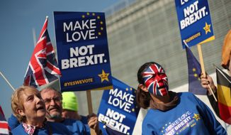 Activists wave flags and hold signs during an anti-Brexit campaign stunt outside EU headquarters during an EU summit in Brussels, Thursday, March 21, 2019. British Prime Minister Theresa May is trying to persuade European Union leaders to delay Brexit by up to three months, just eight days before Britain is scheduled to leave the bloc. (AP Photo/Francisco Seco)
