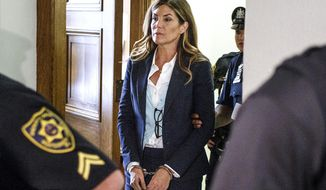 FILE - In this Oct. 24, 2016, file photo former state Attorney General Kathleen Kane leaves court in handcuffs after her sentencing at the Montgomery County Courthouse in Norristown, Pa. Kane is losing her law license, a few months after she began a jail sentence for perjury, obstruction and other counts.The Disciplinary Board of the Supreme Court of Pennsylvania issued a disbarment order on Friday, March 22, 2019. (Dan Gleiter/PennLive.com via AP, Pool, File)