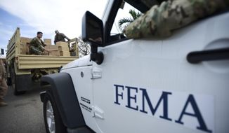 In this Oct. 5, 2017 file photo, Department of Homeland Security personnel deliver supplies to Santa Ana community residents in the aftermath of Hurricane Maria in Guayama, Puerto Rico. A government watchdog has found the Federal Emergency Management Agency wrongly released to a contractor the personal information of 2.3 million survivors of hurricanes Harvey, Irma and Maria and the California wildfires in 2017. (AP Photo/Carlos Giusti, File)