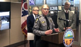 Lt. Col. Marla Gaskill of the Ohio State Highway Patrol explains why safer roads can save lives and prevent troopers from having to deliver bad news to family members of road accidents, at a news conference attended by Gov. Mike DeWine, left, and Department of Public Safety Director Tom Stickrath, right, Friday, March 22, 2019, in Columbus, Ohio. DeWine enlisted patrol members in a push to tie his proposed 18-cent per gallon gas tax increase to public safety. (AP Photo/Andrew Welsh-Huggins)