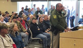"""An overflowing crowd packs the Elko County Commission chamber as Sheriff Aitor Narvaiza presents his case for the county to declare a """"Second Amendment sanctuary"""" in this photo take Wednesday, March 20, 2019 in Elko, Nev. Elko County is one of four rural Nevada counties are joining a """"Second Amendment sanctuary"""" drive that has grown in sheriff's offices and statehouses in several Western U.S. states. (Tim Burmeister/Elko Daily Free Press via AP)"""