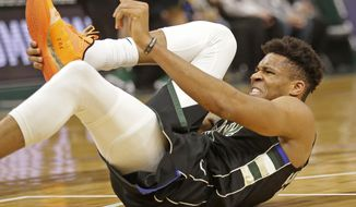 Milwaukee Bucks' Giannis Antetokounmpo grabs his foot during the first half of an NBA basketball game against the Miami Heat, Friday, March 22, 2019, in Milwaukee. (AP Photo/Jeffrey Phelps)