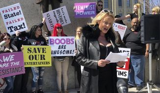 "Adult film star Stormy Daniels reads a statement, protesting the Illinois surcharge on live adult entertainment centers, beneath the statue of Abraham Lincoln at the state Capitol, Friday, March 22, 2019 in Springfield, Ill. The actress famous for her alleged affair with Donald Trump before he became president read a two-minute statement before she was whisked off to a local strip club to sign copies of her book. Daniels, whose real name is Stephanie Clifford, says the tax unfairly ties nude dancing to violence against women and that it ""takes money out of the g-strings of hardworking young dancers."" (AP Photo/John O'Connor)"