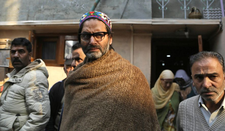 """FILE- In this Thursday, Nov. 10, 2016, file photo, Jammu Kashmir Liberation Front (JKLF) Chairman Yasin Malik, center, walks outside his home after he was detained by Indian police in Srinagar, Indian controlled Kashmir. India has banned a pro-independence group in its portion of Kashmir as part of a crackdown on separatist oganizations. A government statement Friday, March 22, 2019 says the Jammu Kashmir Liberation Front, led by Yasin Malik, has been declared as an """"unlawful association'' to curb the activities of secessionist organizations posing a threat to the country's unity and integrity. (AP Photo/Mukhtar Khan, file)"""