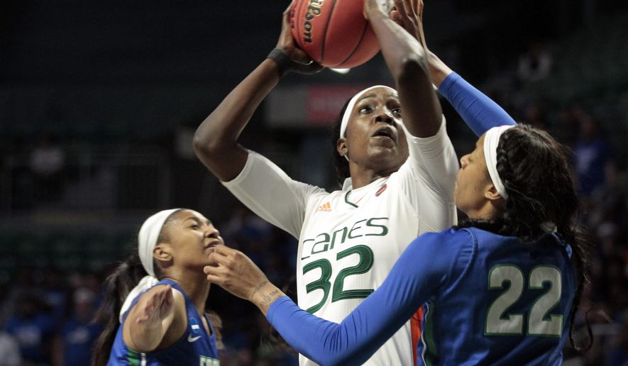 Miami forward Beatrice Mompremier (32) aims for a basket as Florida Gulf Coast guard Destiny Washington-Mabon (22) and guard Davion Wingate (0) defend, during a first round women's college basketball game in the NCAA Tournament in Friday, March 22, 2019, in Coral Gables, Fla. (AP Photo/Luis M. Alvarez)