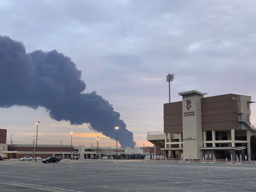 In this Tuesday, March 19, 2019 photo, shows smoke rising from a fire at the Intercontinental Terminals Company near the Deer Park School District's Abshire Stadium in Deer Park, Texas. Officials have lifted an order to remain indoors after several readings showed that the air quality had improved near a scorched petrochemical storage facility in suburban Houston. City officials in Deer Park lifted the order Thursday and reopened roads around the Intercontinental Terminals Company. But residents living near ITC say they're skeptical of what public officials are telling them. (Jeffrey Fountain via AP)