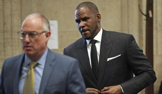 R. Kelly, right, appears in court with his attorney Steve Greenberg, March 22, 2019, for a hearing at the Leighton Criminal Court Building in Chicago. An overseas trip by R. Kelly is in limbo after his criminal attorney asked for more time to provide details to the court about concerts the singer wants to perform next month in Dubai. The hearing only briefly touched on a defense motion this week asking the judge in Kelly's sexual-assault case for permission to travel to earn money from up to five concerts. The filing says Kelly is scrambling to pay bills amid his legal troubles. (E. Jason Wambsgans/Chicago Tribune Via AP, Pool)