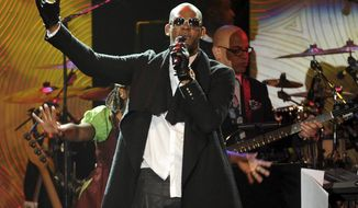 FILE - In this Jan. 25, 2014 file photo, recording artist R. Kelly performs at The 56th Annual Grammy Awards Salute to Industry Icons with Clive Davis in Beverly Hills, Calif. A Chicago judge is expected to rule on whether to let R. Kelly travel overseas to perform several concerts to help the cash-strapped singer pay legal and other bills as he faces sex-abuse charges. A hearing Friday, March 22, 2019, follows a defense motion saying the 52-year-old singer hopes to do up to five April concerts in Dubai. (Photo by Frank Micelotta/Invision/AP, File)