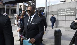R. Kelly, front, leaves the Leighton Criminal Court after a hearing on Friday, March 22, 2019, in Chicago. (AP Photo/Matt Marton)