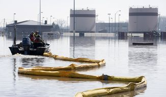 In this March 18, 2019, photo released by the U.S. Air Force, environmental restoration employees deploy a containment boom from a boat on Offutt Air Force Base in Neb., as a precautionary measure for possible fuel leaks in the flooded area. Surging unexpectedly strong and up to 7 feet high, the Missouri River floodwaters that poured on to much the Nebraska air base that houses the U.S. Strategic Command overwhelmed the frantic sandbagging by troops and their scramble to save sensitive equipment, munitions and aircraft. (Delanie Stafford, The U.S. Air Force via AP)