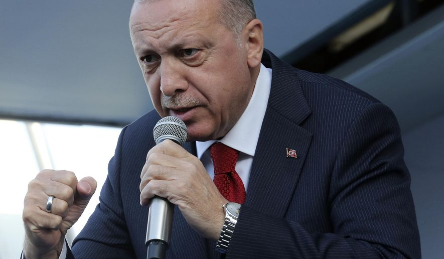 Turkey's President Recep Tayyip Erdogan addresses the supporters of his ruling Justice and Development Party during a rally in Kutahya, Turkey, Thursday, March 21, 2019. Erdogan has again screened clips of a video taken by the Christchurch mosque gunman, a day before the foreign minister of New Zealand _ which is trying to stop its use _ is due in Turkey.(Presidential Press Service via AP, Pool)