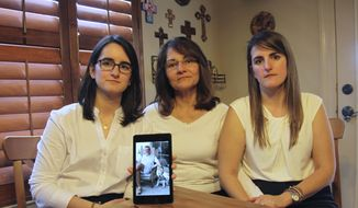 FILE - In this Feb. 15, 2019 file photo, Dennysse Vadell sits between her daughters Veronica, right, and Cristina holding a digital photograph of father and husband Tomeu who is currently jailed in Venezuela, in Katy, Texas, Friday. Tomeu Vadell is one of six executives from Houston-based Citgo who has spent 15 months jailed in Venezuela on what their families say are trumped-up corruption charges. (AP Photo/John L Mone, File, File)