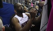 Miami Heat guard Dwyane Wade signs for fans after an NBA basketball game against the Washington Wizards, Saturday, March 23, 2019, in Washington. The Heat won 113-108. (AP Photo/Nick Wass)