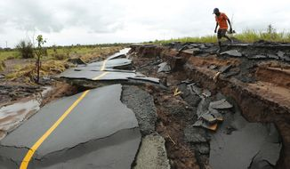 A man passes through a section of the road damaged by Cyclone Idai in Nhamatanda about 50 kilometres from Beira, in Mozambique, Friday March, 22, 2019. As flood waters began to recede in parts of Mozambique on Friday, fears rose that the death toll could soar as bodies are revealed. (AP Photo/Tsvangirayi Mukwazhi)