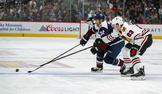 Colorado Avalanche center Colin Wilson (22) and Chicago Blackhawks defenseman Carl Dahlstrom (63) chase the puck during the second period of an NHL hockey game, Saturday, March 23, 2019 in Denver. (AP Photo/Jack Dempsey)