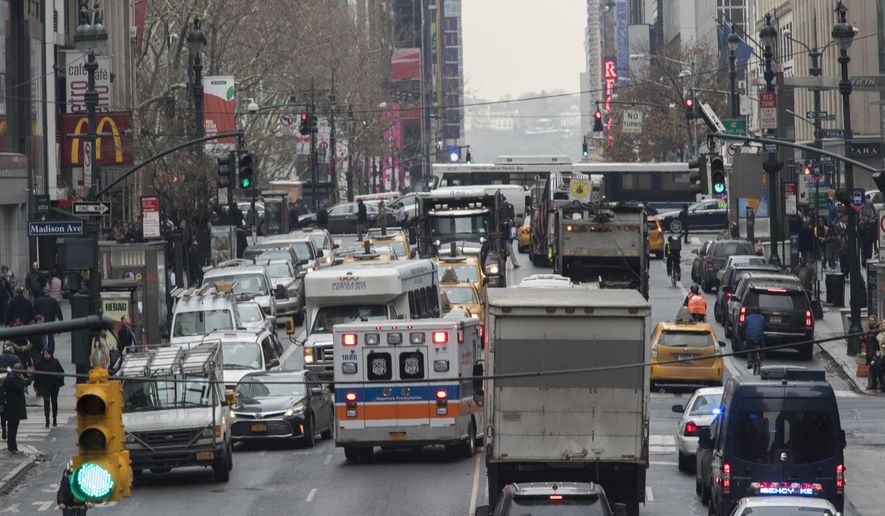FILE- In this Jan. 11, 2018 photo, an ambulance is seen driving in the wrong lane to get around traffic on 42nd Street in New York. New York Gov. Andrew Cuomo and fellow Democrats who control the Legislature are making tough choices as they try to get a spending plan in place by an April 1 deadline. A proposal to implement motor vehicle congestion pricing in Manhattan to fund the city's ailing transit system is still alive in the negotiations. (AP Photo/Mary Altaffer)