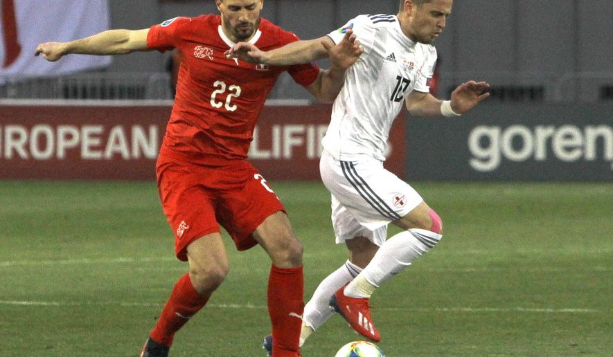 Switzerland's Fabian Schar, left, and Georgia's Jano Ananidze challenge for the ball during the Euro 2020 group D qualifying soccer match between Georgia and Switzerland at Boris Paichadze Erovnuli stadium in Tbilisi, Georgia, Saturday, March 23, 2019. (AP Photo/Shakh Aivazov)