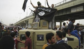 In this Sunday, March 30, 2014, photo, Islamic State group militants hold up their flag as they patrol in a commandeered Iraqi military vehicle in Fallujah, 40 miles (65 kilometers) west of Baghdad, Iraq. (AP Photo) **FILE**