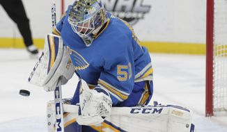 St. Louis Blues goaltender Jordan Binnington (50) makes a stick-save in the first period of an NHL hockey game against the Tampa Bay Lightning, Saturday, March 23, 2019, in St. Louis. (AP Photo/Tom Gannam)