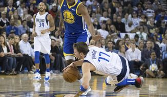Dallas Mavericks forward Luka Doncic (77) collides with Golden State Warriors center Kevon Looney in the first half of an NBA basketball game Saturday, March 23, 2019, in Oakland, Calif. (AP Photo/John Hefti)