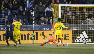 Philadelphia Union's David Accam, left, scores a goal against Columbus Crew's Joseph Bendik, back right, during the first half of an MLS soccer match, Saturday, March 23, 2019, in Chester, Pa. (AP Photo/Chris Szagola)