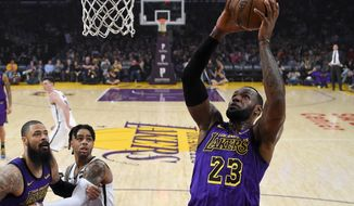 Los Angeles Lakers forward LeBron James, right, shoots as center Tyson Chandler, left, and Brooklyn Nets guard D'Angelo Russell watch during the first half of an NBA basketball game Friday, March 22, 2019, in Los Angeles. (AP Photo/Mark J. Terrill)