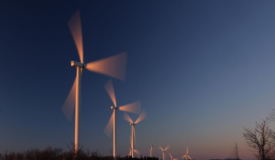 Wind turbines are bathed in the first rays of sunlight at the Saddleback Ridge Wind Project, Wednesday, March 20, 2019, in Carthage, Maine. (AP Photo/Robert F. Bukaty)