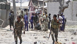 Somali government soldiers run to take positions during ongoing fighting with gunmen, after a suicide car bomb attack on a government building in the capital Mogadishu, Somalia, Saturday, March 23, 2019. Al-Shabab gunmen stormed into the government building following a suicide car bombing at the gates on Saturday, a police officer said, in the latest attack by Islamic extremist fighters in the Horn of Africa nation. (AP Photo/Farah Abdi Warsameh)
