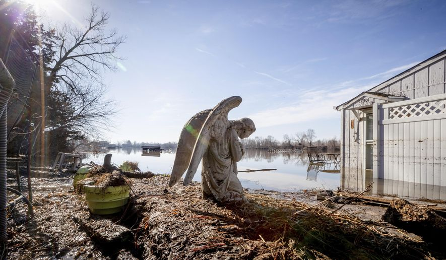 An angel statuary graces a yard near Hansen Lake Friday, March 22, 2019, in Bellevue, Neb. Residents were allowed into the area for the first time since floodwaters overtook several homes. Flooding in Nebraska has caused an estimated $1.4 billion in damage. The state received Trump's federal disaster assistance approval on Thursday. (Kent Sievers/Omaha World-Herald via AP)