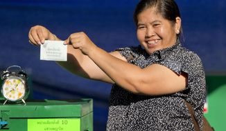 A Thai voter with a ballot paper in her hand, poses at a polling station in Bangkok, Thailand, Sunday, March 24, 2019, during the nation's first general election since the military seized power in a 2014 coup. (AP Photo/Gemunu Amarasinghe)