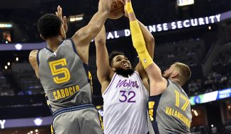 Minnesota Timberwolves center Karl-Anthony Towns (32) shoots against Memphis Grizzlies center Jonas Valanciunas (17) and forward Bruno Caboclo (5) in the second half of an NBA basketball game Saturday, March 23, 2019, in Memphis, Tenn. (AP Photo/Brandon Dill)