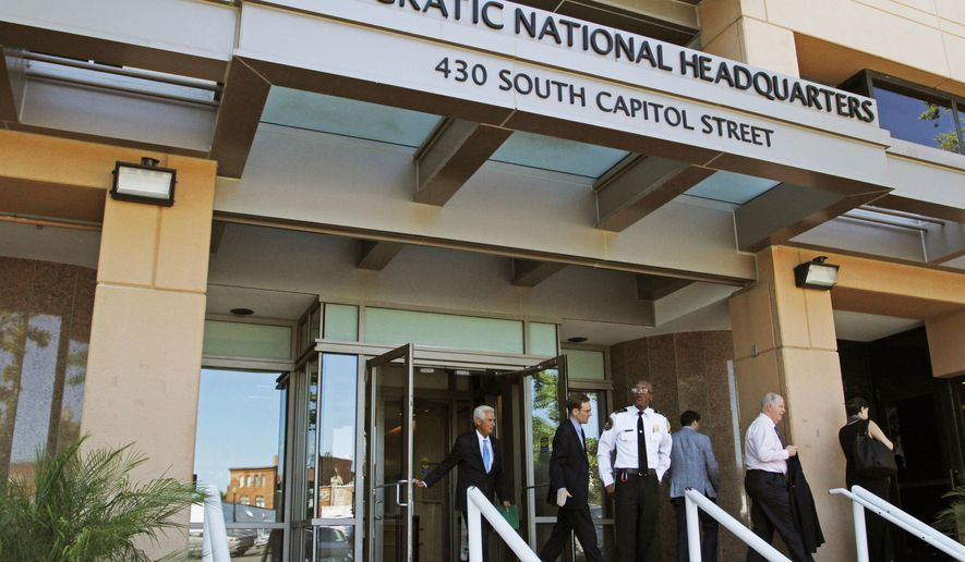In this June 14, 2016 file photo, people stand outside the Democratic National Committee headquarters in Washington. (AP Photo/Paul Holston, File)