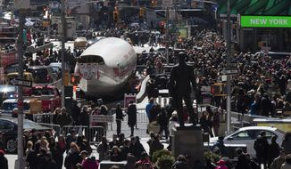 """A Lockheed Constellation L-1649A Starliner, known as the """"Connie, is parked in New York's Times Square during a promotional event, Saturday, March 23, 2019, in New York. The vintage commercial airplane will serve as the cocktail lounge outside the TWA Hotel at JFK airport. (AP Photo/Mary Altaffer)"""