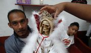 In this Feb. 19, 2017 photo, a man holds a Death Saint statue as his wife places a crown and his son looks on, at Mercy Church on the edge of Mexico City's Tepito neighborhood. To followers, she's known as the Death Saint, the White Girl, the Skinny One, or just Sister _ and a life-transforming answer to their prayers. To the Vatican, though, she's an irritation seen as leading the faithful astray. (AP Photo/Marco Ugarte)