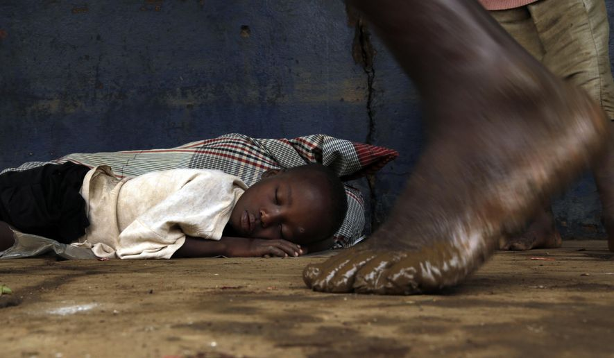 A displaced young boy sleeps on the floor at a school in Buzi district, 200 kilometers (120 miles) outside Beira, Mozambique, on Saturday, March 23, 2019. People left the cyclone-shattered city of Beira for the town of Buzi, which for a week people had been fleeing to with little but their clothes. (AP Photo/Themba Hadebe)