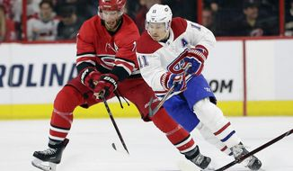 Carolina Hurricanes' Jordan Staal, left, and Montreal Canadiens Brendan Gallagher (11) chase the puck during the first period of an NHL hockey game in Raleigh, N.C., Sunday, March 24, 2019. (AP Photo/Gerry Broome)