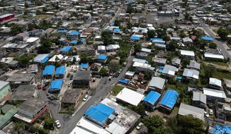 This June 18, 2018, file photo shows an aerial view of the Amelia neighborhood in the municipality of Catano, east of San Juan, Puerto Rico. (AP Photo/Dennis M. Rivera, File)