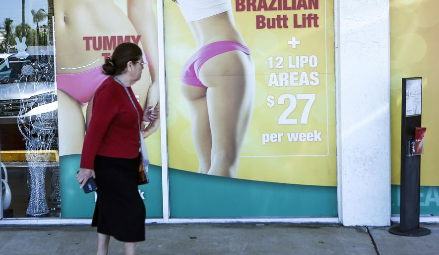 In this Friday, March 22, 2019 photo, a window display advertises low-cost cosmetic procedures outside a surgery clinic in Miami. South Florida has become a hub for the freewheeling industry in trendy cosmetic surgeries, drawing a boom in medical tourism. However, complications and even deaths of several out-of-state women in recent years have spiked concerns over safety of the cosmetic procedures, prompting a bill before the Florida Legislature this year to impose stricter regulations. (AP Photo/Ellis Rua)