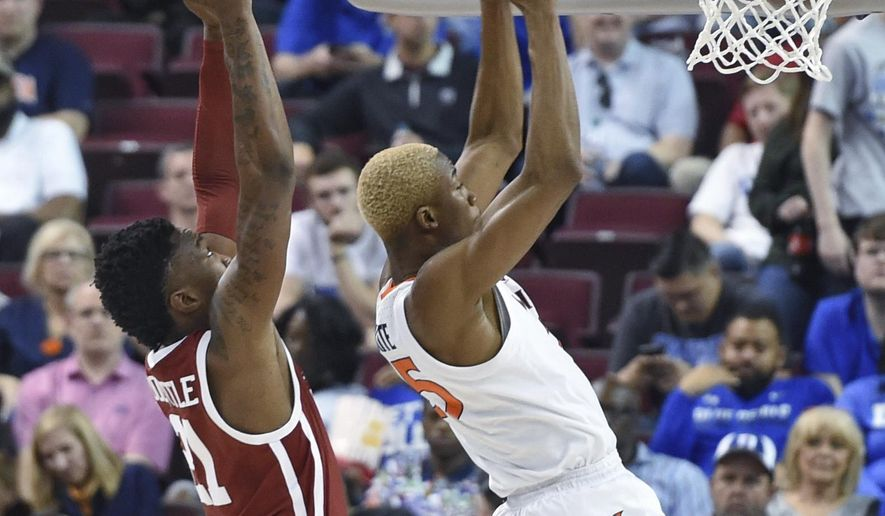 Virginia's Mamadi Diakite (25) pulls in a rebound while defended by Oklahoma's Kristian Doolittle (21) during the second half of a second-round men's college basketball game in the NCAA Tournament in Columbia, S.C. Sunday, March 24, 2019. (AP Photo/Richard Shiro)
