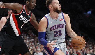 Detroit Pistons forward Blake Griffin, right, spins to the basket next to Portland Trail Blazers forward Al-Farouq Aminu during the first half of an NBA basketball game in Portland, Ore., Saturday, March 23, 2019. (AP Photo/Steve Dipaola)
