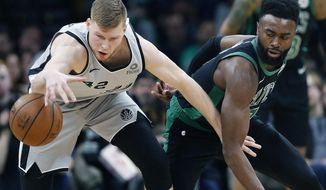 San Antonio Spurs' Davis Bertans (42) and Boston Celtics' Jaylen Brown, right, battle for the ball during the first half of an NBA basketball game in Boston, Sunday, March 24, 2019. (AP Photo/Michael Dwyer)