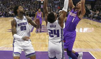 Phoenix Suns guard Devin Booker, right, goes up for the shot against Sacramento Kings guard Buddy Hield, center, as Kings center Willie Cauley-Stein, left, watches during the first quarter of an NBA basketball game Saturday, March 23, 2019, in Sacramento, Calif. (AP Photo/Rich Pedroncelli)