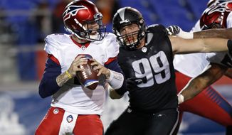 Memphis Express quarterback Johnny Manziel (2) looks for a receiver as he's pressured by Birmingham Iron defensive lineman Jake Payne (99) during a Birmingham Iron at Memphis Express AAF football game, Sunday, March 24, 2019, at Liberty Bowl Memorial Stadium in Memphis, Tenn. against the Memphis won in overtime 31-25. (AP Photo/Wade Payne)