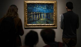 Visitors look at 'Starry Night' (1888) by Vincent van Gogh during the preview for the upcoming Van Gogh and Britain exhibition at Tate Britain, London, Monday March 25, 2019.  The Van Gogh and Britain exhibition takes a new look at the artist through his relationship with Britain, and how he was inspired by British art, literature and culture. (Victoria Jones/PA via AP)