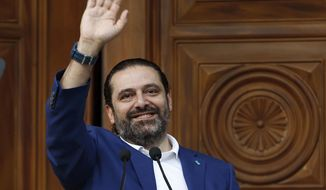 FILE -- In this May, 11, 2018 file photo, Lebanese Prime Minister Saad Hariri, waves to his supporters at his house in downtown Beirut, Lebanon. According to his office,  Hariri, 48, was admitted to a Paris hospital Monday, March 25, 2019, where he underwent an hour-long angioplasty procedure, used to treat blocked arteries. Hariri is expected to be discharged Monday. (AP Photo/Bilal Hussein, File)