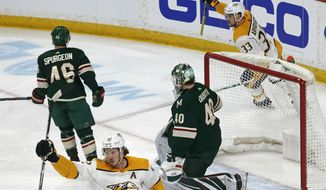 Nashville Predators' Viktor Arvidsson, top right, of Sweden, celebrates a goal off Minnesota Wild goalie Devan Dubnyk, right, by Nashville Predators' Ryan Johansen, lower left, during the first period of an NHL hockey game Monday, March 25, 2019, in St. Paul, Minn. (AP Photo/Jim Mone)