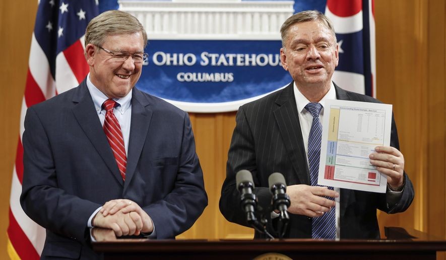Ohio State Reps. Bob Cupp, R-Lima, left, and John Patterson, D-Jefferson, announce their proposed overhaul of Ohio's school funding formula at the Statehouse in Columbus, Monday, March 25, 2019. (AP Photo/John Minchillo)