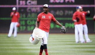 Washington Nationals center fielder Victor Robles (16) carries a bucket of baseballs before an exhibition baseball game against the New York Yankees, Monday, March 25, 2019, in Washington. (AP Photo/Nick Wass)