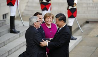 Chinese President Xi Jinping, is welcomed by French President Emmanuel Macron, 2nd right, with German Chancellor Angela Merkel, right, and European Commission President Jean-Claude Juncker, left, prior to their meeting at the Elysee presidential palace in Paris, Tuesday, March 26, 2019. Merkel and Juncker are meeting with Macron as they prepare for a possibly chaotic Brexit and a crucial summit with China. (AP Photo/Francois Mori)